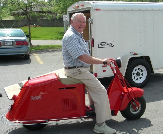 Man riding a red 1946 Cushman Motorscooter