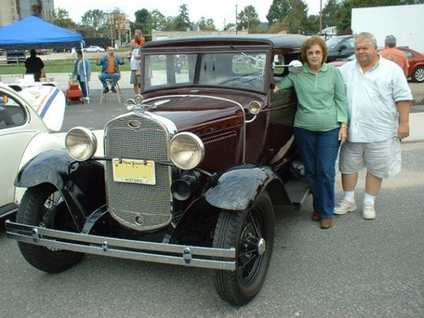 Man and woman standing next to Maroon 1931 Ford Victoria