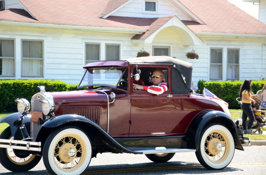 Dark red antique vehicle with white and gold tires and black trim