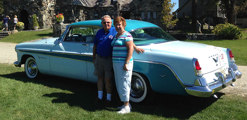 Man and woman standing infront of teal antique car