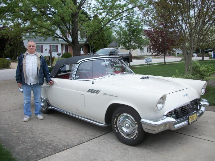 Man standing next to white 57 Thunderbird