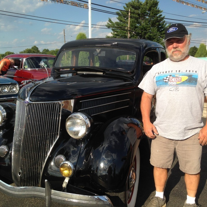 Mand standing next to black 1936 ford