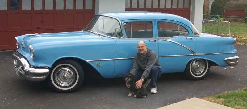 Man with dog crouching infront of light blue antique car